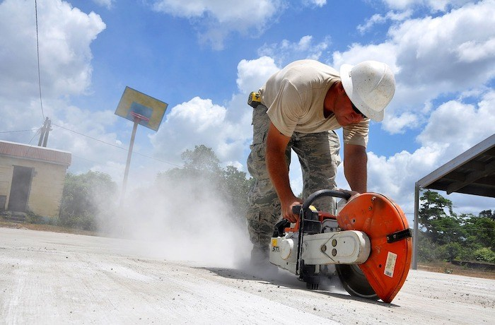 strong construction worker with concrete saw and hard hat with lots of dust from the saw
