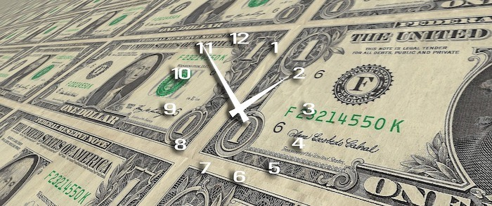 dollars lined up side by side with clock face superimposed on top