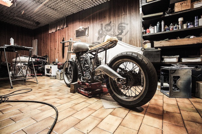 bobber style motorcycle in a garage with wood paneling