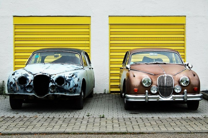 white building with yellow garage doors and two vintage cars parked