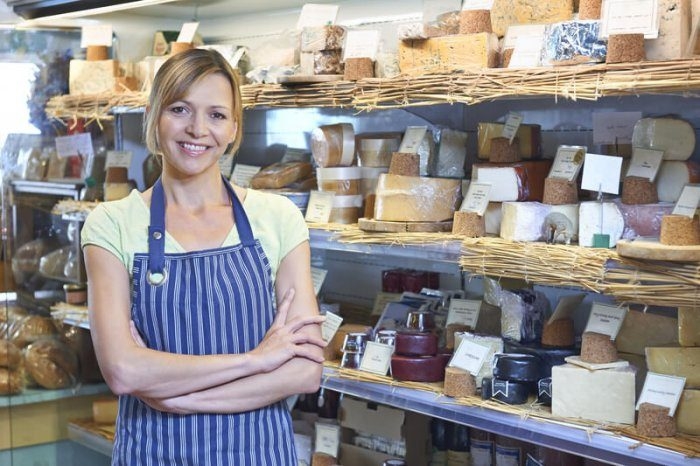woman standing next to various types of cheese in a small local business