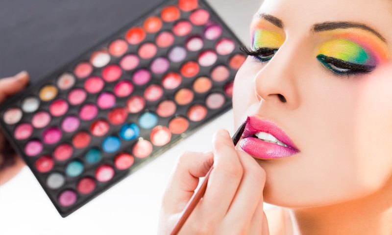 A young woman with bright eyeshadow getting her makeup done.