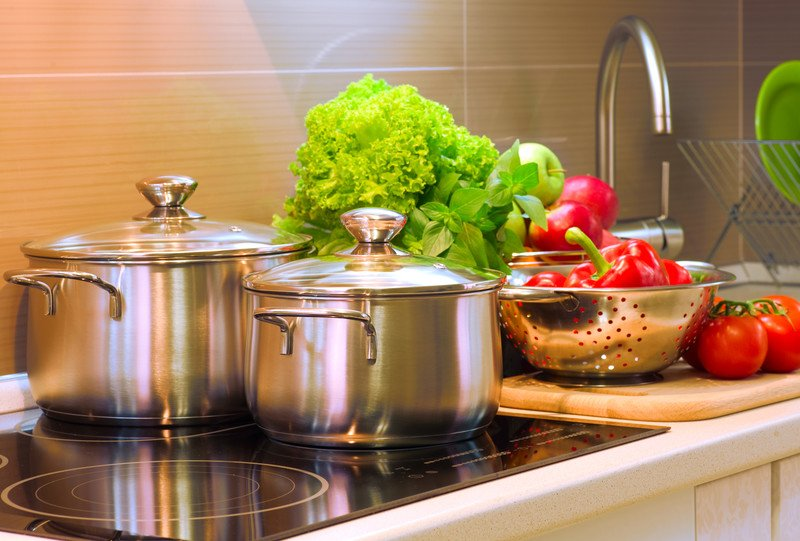 A stovetop with two stainless steel pots and various fresh ingredients.