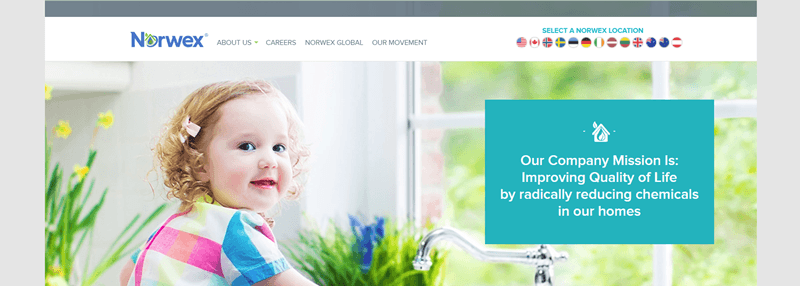 Norwex website screenshot showing a toddler in a brightly lit kitchen, smiling at the camera.
