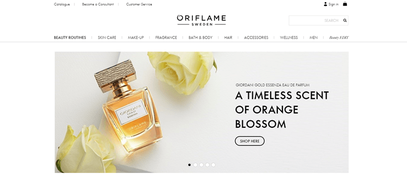 Oriflame website screenshot showing a white tabletop with two roses and a bottle of perfume.
