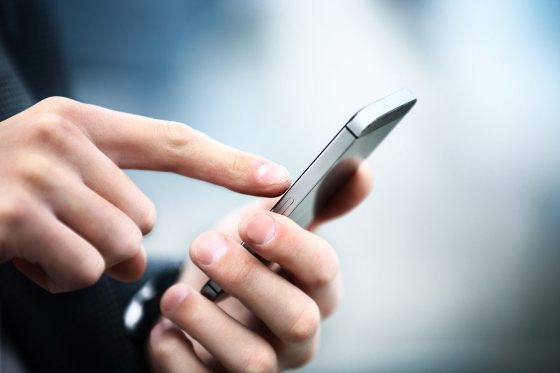Close up image of a man using a touch screen on his cellphone