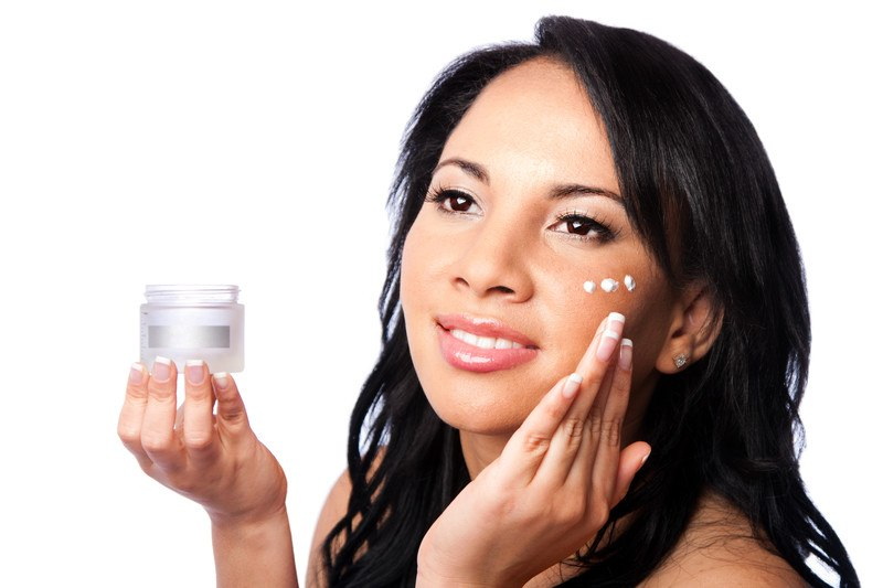 Young woman applying skincare in small dots under her eye,