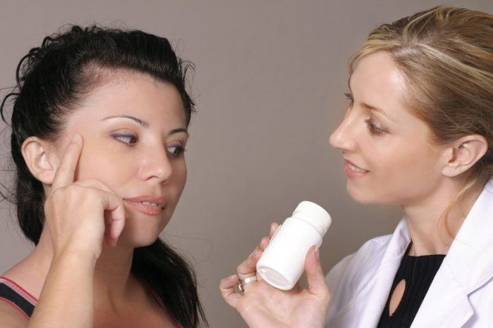Image of two women, where one is showing a supplement bottle to the other.