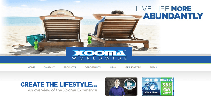Xooma Worldwide website screenshot showing a slightly distorted image of a couple in reclining deck chairs on the beach, facing the water.