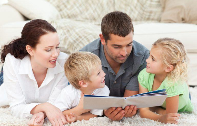 Young family reading a children's book on the floor