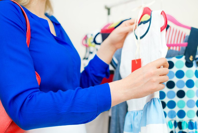 A woman in a blue shirt picking out a child's dress