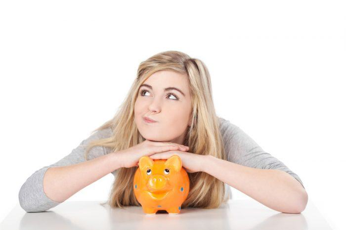 Young girl with her arms folded over an orange piggy bank