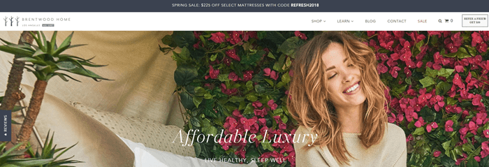 Brentwood Home website screenshot showing a young brown-haired woman against a floral background. She's grinning and has her eyes shut.