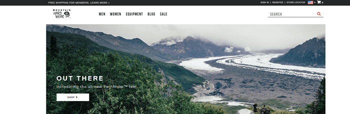 Mountain Hardwear website screenshot showing an outdoors scene with various mountains and low clouds.