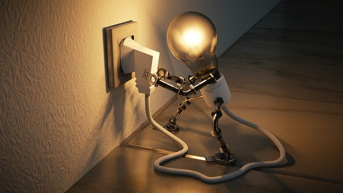 animatronic lightbulb plugging itself into a wall