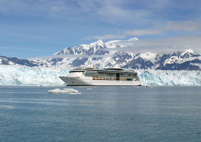 large cruise ship in the arctic with an iceberg in the background representing cruise-related affiliate programs