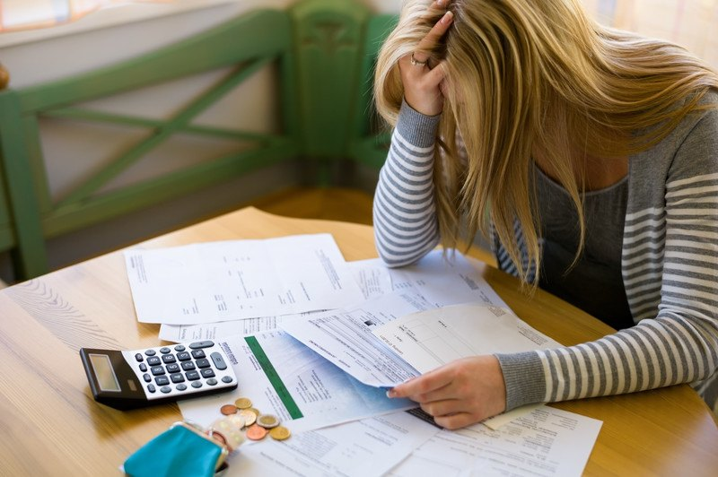 Blonde woman sitting at a table with her head in her hand looking at unpaid bills.