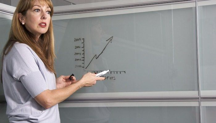 female college teacher writing on a transparent whiteboard drawing a graph which represents the best education affiliate programs