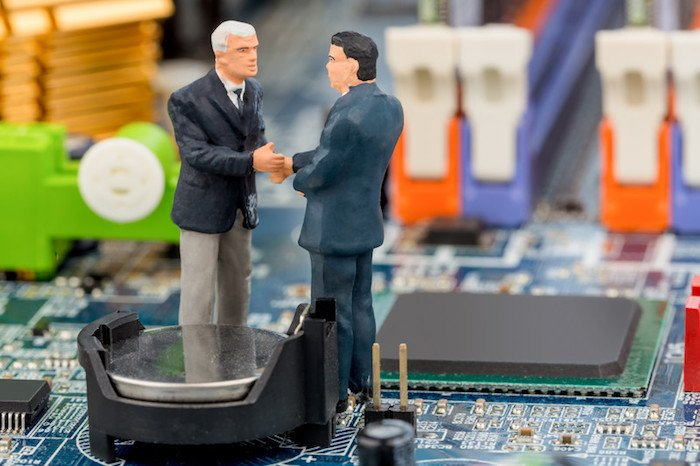 two toy men shaking hands on a computer chip representing the best electronics affiliate programs