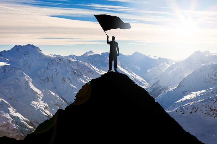 man at the top of a mountain peak with a flag showing best personal development affiliate programs