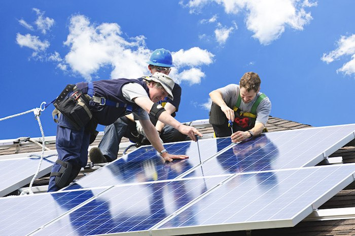 three men installing solar panels on a residential roof representing best solar energy affiliate programs