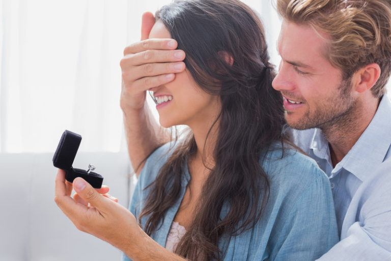 Man covering a woman's eyes while holding an engagement ring in front of her