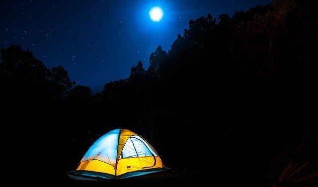A colored tent lit from the inside in a dark environment with the moon shining