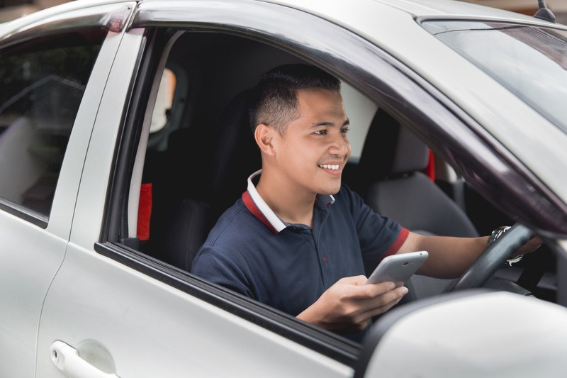 Image of a young man in a silver car using his phone making money doing rideshare