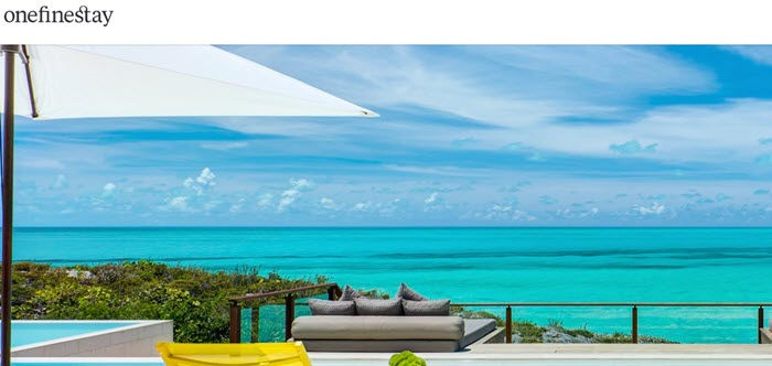 OneFineStay website screenshot showing a beautiful scenic image looking out from a vacation home onto the clear blue ocean.