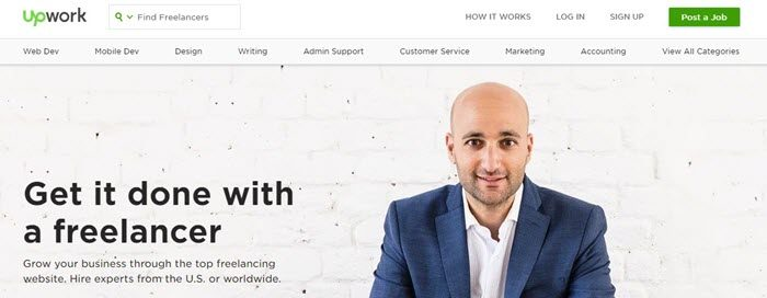 Upwork website screenshot showing an image of a bald man in a blue suit in front of a white brick wall.