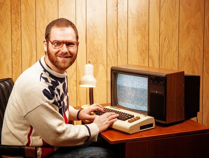 classic nerd trope photo of red hairded man with large glasses sitting at a 70's style computer with wood paneling in the background showing best nerd affiliate programs