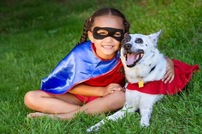 young girl in superhero costume with spotted dog in a cape as the title image for the best superhero affiliate programs