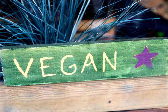 """green sign with blue plant that says """"Vegan"""" to represent the best vegan affiliate programs"""