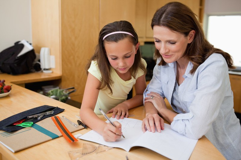 Mother and daughter sitting at a table during homeschooling