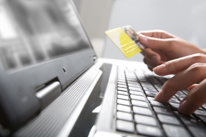 Hands on a keyboard with one holding a credit card