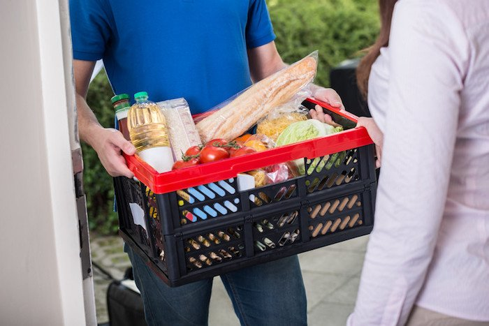 man in blue shirt with a crate full of groceries he's delivering to make money with a food delivery side gig app