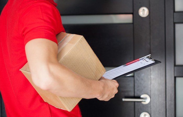 man with red polo shirt and package under arm with form to sign. he is working a package delivery gig from an app making money