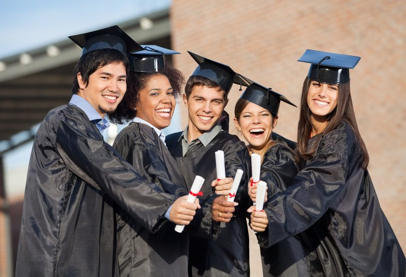 Image of five students wearing graduation gowns and caps, while holding diplomas