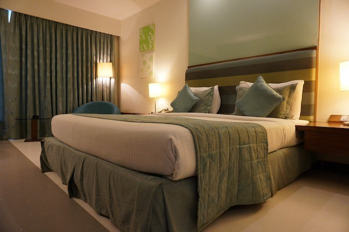 Image of a nicely lit hotel room with a large bed