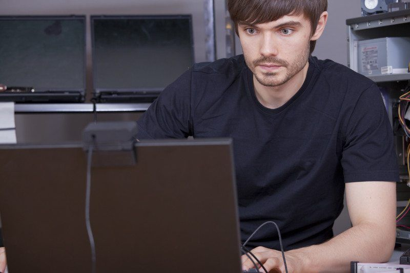 Image of a young man in a black shirt typing on a computer