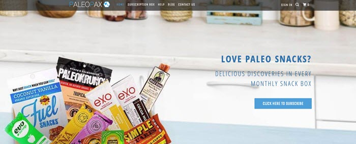 PaleoPax website screenshot showing the open box with snacks on a kitchen counter.