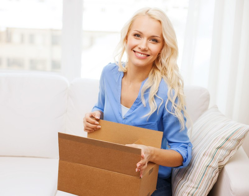 Image shows a young blonde woman opening a subscription box