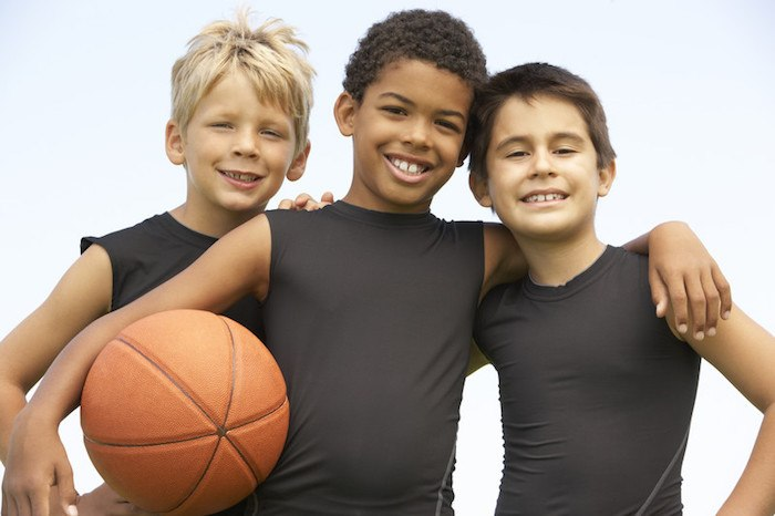 three boys about 10 years old smiling at the camera with a basketball in the hand as the title image for basketball affiliate programs