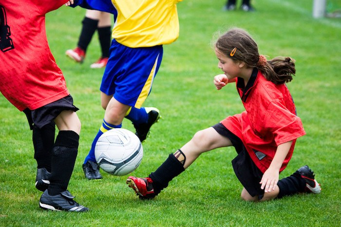 young girl in soccer uniform doing a slide tackle on the soccer field showing the best soccer affiliate programs