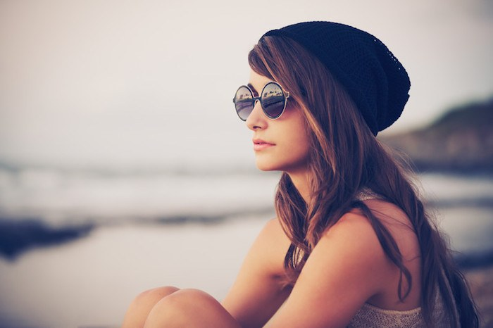 young woman sitting on the beach with vintage fashion sunglasses and a black beanie hat