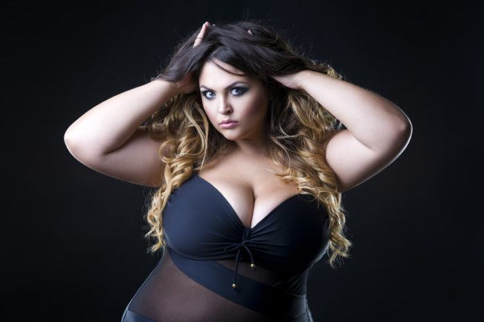 plus size model wearing black lingerie with black background