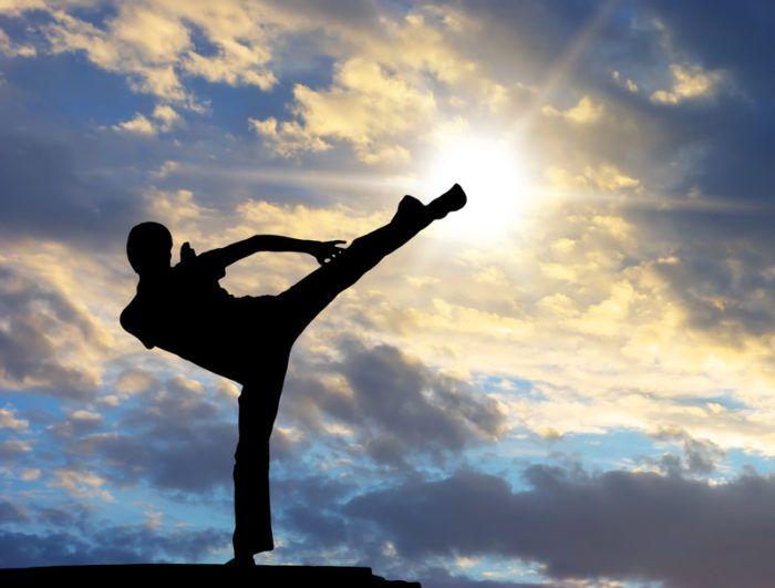 man doing kung fu kick showing mastery, growth, and skill