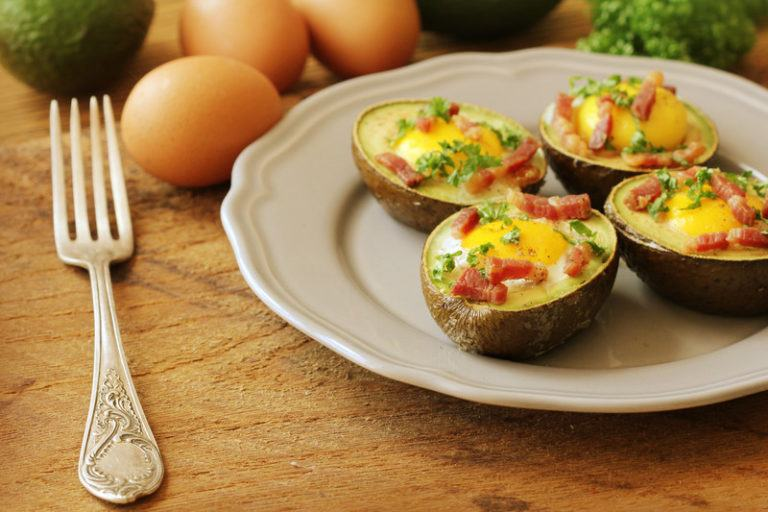 baked avocado with egg, cheese, and bacon in the middle
