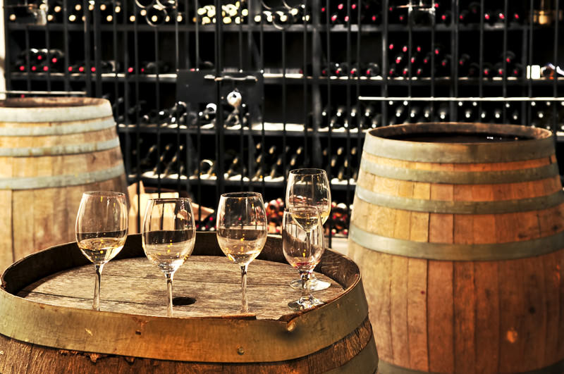 wine tasting club with old wine barrel as table and empty wine glasses and bottles stacked in the background
