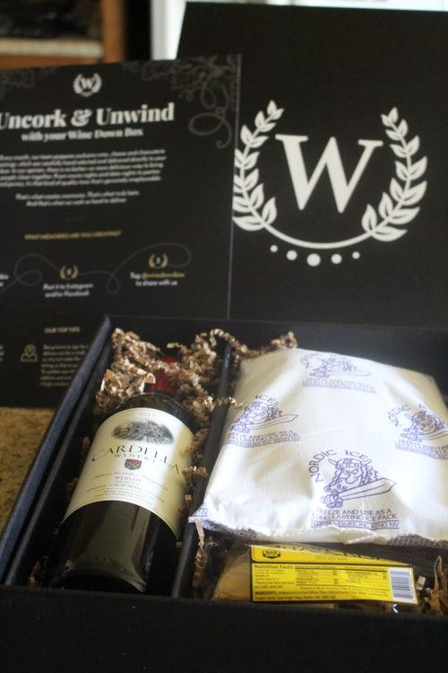 wine subscription box with bottle of wine, ice pack, cheese, and salami